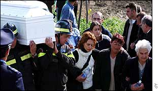 Families walk alongside the coffins as they carried by Italian rescuers and firefighters