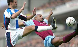 Lucas Neill contests a ball with Villa's Dion Dublin