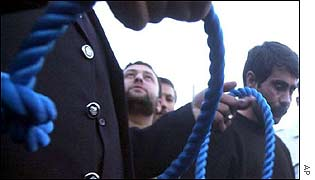 Iranian officials with a noose for a convicted killer (right)