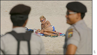 Indonesian police watch over a Bali beach as a tourist sunbathes