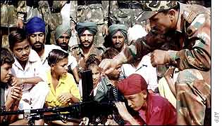 Soldiers at a camp near Amritsar, letting a child inspect his gun