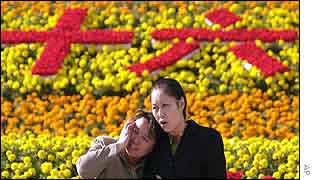 People walk past a flower garden featuring Chinese characters which mean