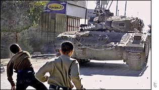 Stone throwing Palestinian boys face Israeli tank