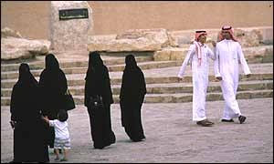 Women in black pass men on a Riyadh street