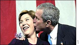 US First Lady Laura Bush (l) receives a birthday kiss from her husband, US President George Bush
