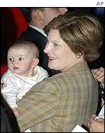 Laura Bush holds a young baby during a campaign rally in South Dakota