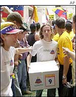 A member of the opposition carries a box with signatures for the referendum
