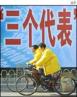 Two cyclists pass a billboard with the characters for the