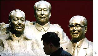 A Chinese man is silhouetted against busts of Chinese Communist leaders Deng Xiaoping, left, Mao Zedong, centre, and Jiang Zemin