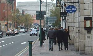 People walk past pubs in Birmingham's Broad Street