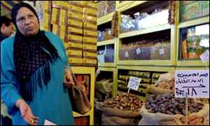 Egyptian woman buys dates in a Cairo market marked Saddam Hussein Mass Destruction