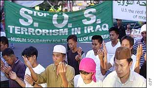 A group of Filipino Muslims pray outside the US embassy in Manila during an anti-US rally