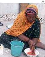 A woman washes her hands after circumcising a Somali girl