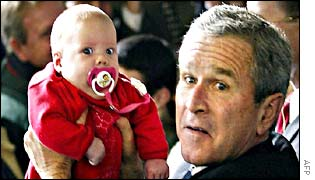 George W Bush holds a baby at a rally