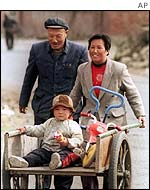 A couple wheeling a child in a handcart