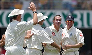 Simon Jones is congratulated by his team-mates after taking England's first wicket