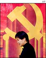 A woman walks past a banner the hammer and sickle, the emblem of the Communist Party