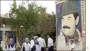 Iraqis walk past a billboard of Saddam Hussein
