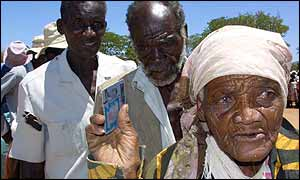 People queuing for food aid with their identity cards