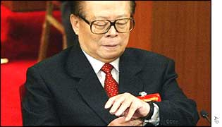 Jiang Zemin checks his watch after delivering his speech at the congress