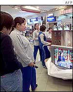 Shoppers look at televisions in shop