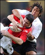 Wales fly-half Stephen Jones is tackled by opposite number Nicky Little
