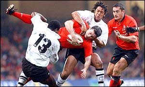 Stephen Jones is tackled by the Fijian defence