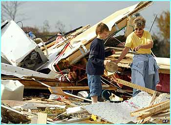 People in Tennessee clear through the mobile home of their neighbours, who were killed by the tornadoes
