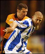 Brighton's Graham Barrett holds off the challenge of Dennis Irwin