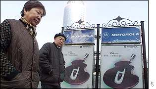 Couple walk past Motorola billboards in Beijing