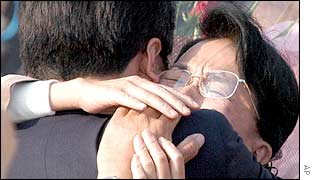 Kidnap survivor Fukie Hamamoto (right) cries as she is hugged by a family member