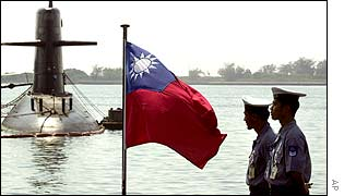 Two Taiwanese sailors stand guard, as submarine is seen in the background, Tsoying Naval Base