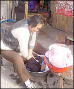 Woman street trader does her laundry as she waits for customers