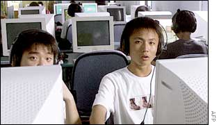 Chinese young men surf the internet at a cyber cafe in Shanghai, 18 June 2002.