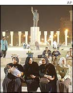 Iraqis sit near a statue of Saddam Hussein