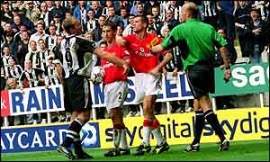 Roy Keane swings an arm at Alan Shearer before being sent off at St James' Park