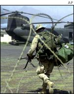 US soldier from the 101st Airborne walks past a Chinook helicopter