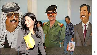 An Iraqi woman walks past portraits of Saddam Hussein