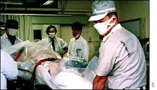 Hospital workers in Tokaimura, Japan, wrap a patient in a polythene sheet during a radiation leak in 1999