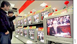 Chinese shopper watch Jiang Zemin on TV as he addresses the closing session of the 16th Communist Party Congress