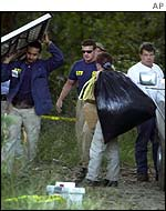 Federal investigator removes bag of evidence from woods in Baton Rouge