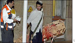 Jewish settlers carry blood-stained stretcher