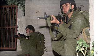 Israeli soldiers aim at a house