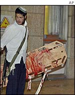 Jewish settler carries blood-stained stretcher