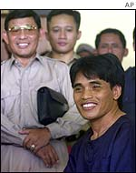 Bali bombing suspect Amrozi (right) poses for reporters with police