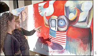 An Iraqi woman explains to her daughter look at a painting expressing anti-U.S ideas at Saddam Art Centre in Baghdad,.