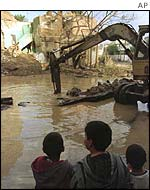 Children look at some of the devastation caused  by Operation Desert Fox