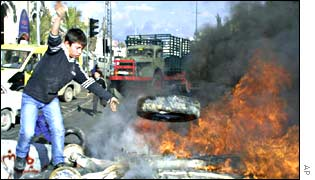 A Palestinian boy tosses a tire into a fire at a road-block near Bethlehem