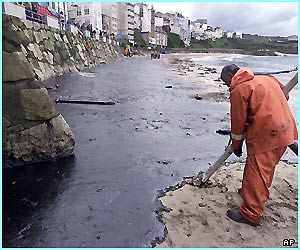 An emergency worker uses a special vacuum cleaner to clean oil off the beach in Malpica