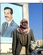 An Iraqi man stands in front of a picture of Saddam Hussein